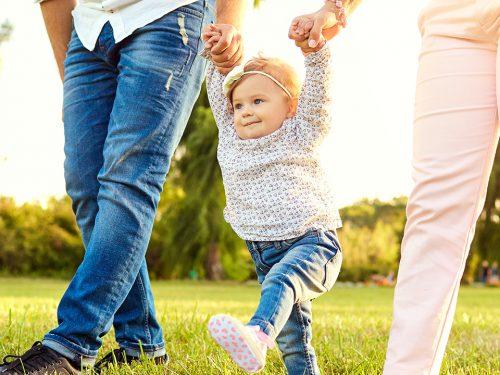 Kind Hand in Hand mit Eltern